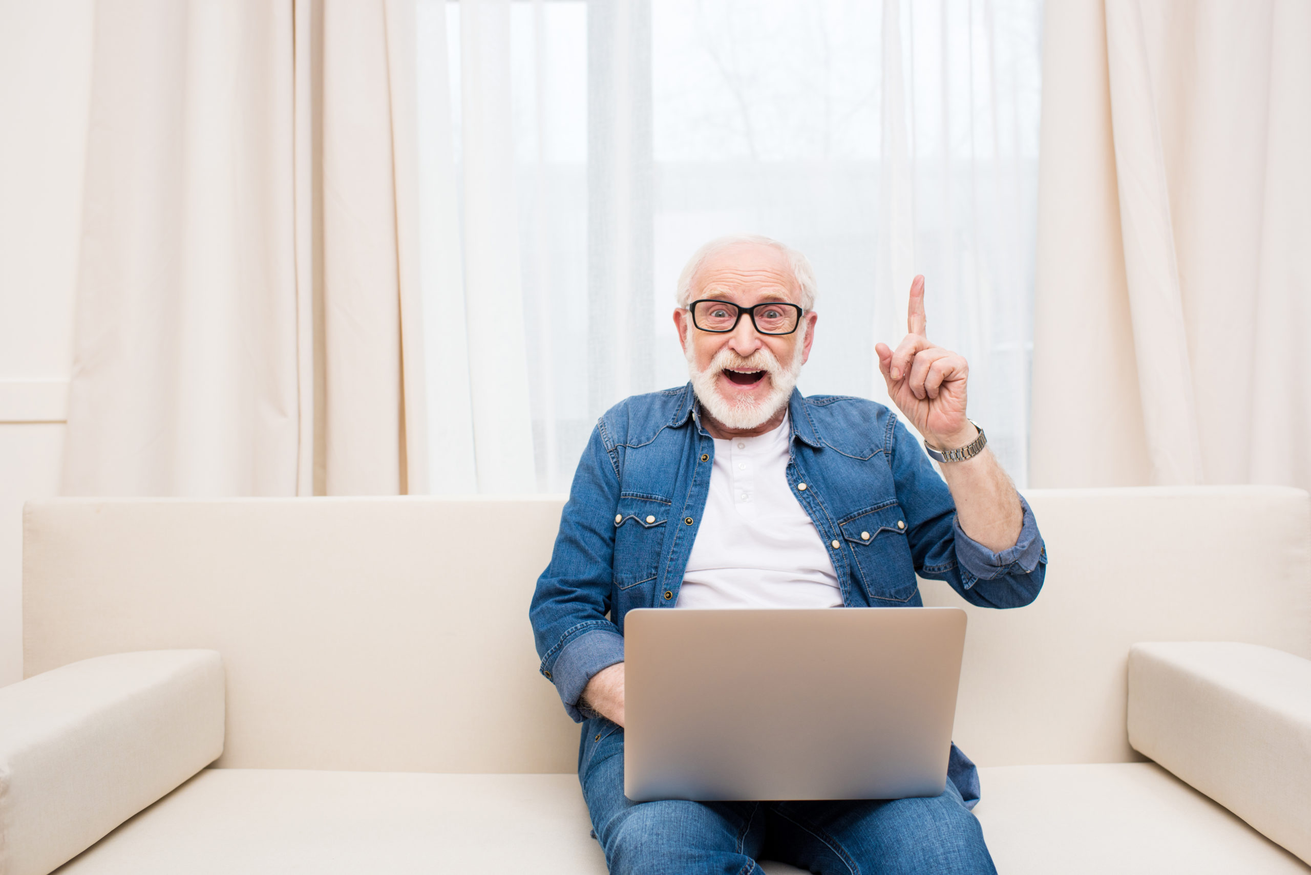 Smiling senior man using laptop and pointing up with finger
